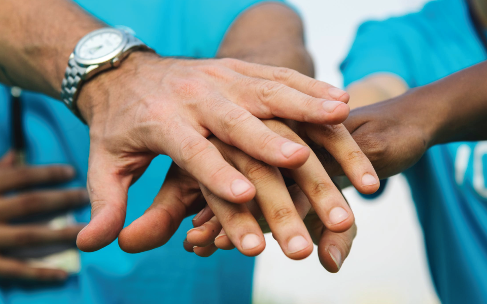 Workers putting hands together as a team